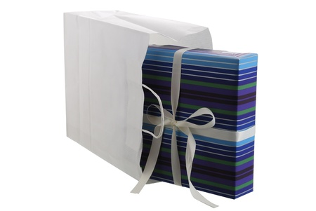 Festive present box wrapped in striped blue paper sticking out from white paper bag isolated on white background Stock Photo
