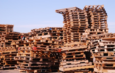 Stacks of used wooden pallets stored under open sky Stock Photo