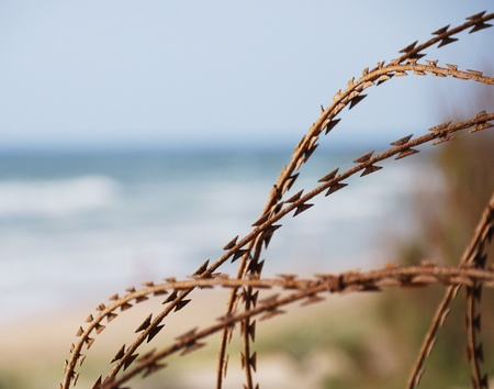 Border fence of rusty barbed wire on blurred blue sea background  Stock Photo - 9646289