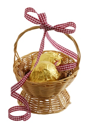 Two chocolate eggs wrapped  golden foil in Easter straw interwoven basket decorated with ribbon isolated on white background