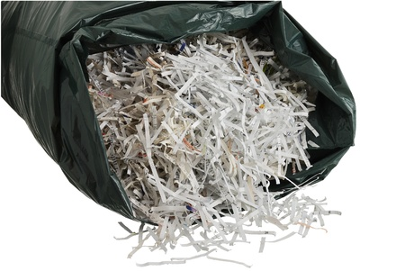 Black plastic garbage bag filled with shredded paper isolated on white background photo
