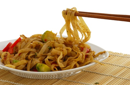Pad Thai dish on straw pad with chopsticks isolated on white background