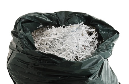 Black plastic garbage bag filled with shredded paper isolated on white background Stock Photo