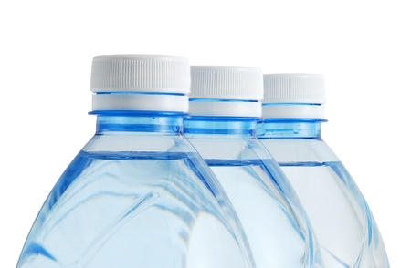 Three plastic mineral water bottles with white cap in row isolated on white background Stock Photo