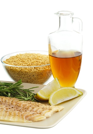 Mediterranean diet dinner ingredients including fresh fish, brown rice, herbs, lemon and olive oil photo