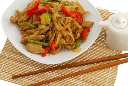 Pad Thai dish on straw pad with chopsticks and soy sauce isolated on white background