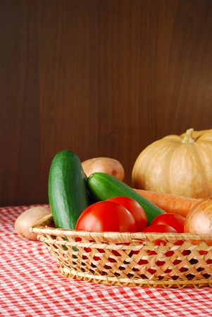 Autumn vegetables mix including onion, carrot, tomatoes, potatoes, cucumbers and pumpkin on red-white tablecloth