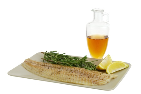 Mediterranean diet dinner ingredients including fresh fish fillet, herbs, lemon and olive oil isolated on white background