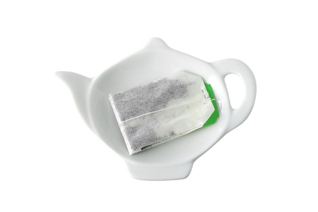 Teabag on teapot shaped saucer isolated on white background Stock Photo