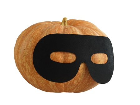 Small Halloween orange pumpkin in black   masquerade mask looking aside  isolated on white background Stock Photo