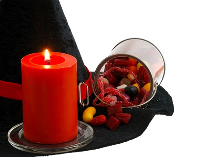 Halloween candies and burning orange candle on edge of witch hat isolated on white background