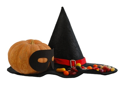 Halloween candies and masqueraded pumpkin on edge of black witch hat isolated on white background