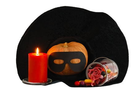 Halloween candies, burning orange candle and masqueraded pumpkin inside black witch hat isolated on white background Stock Photo