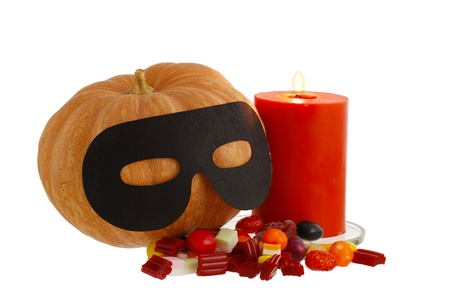Halloween candies, burning orange candle and masqueraded pumpkin isolated on white background