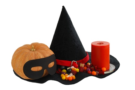 Halloween candies, burning orange candle and masqueraded pumpkin on edge of black witch hat isolated on white background