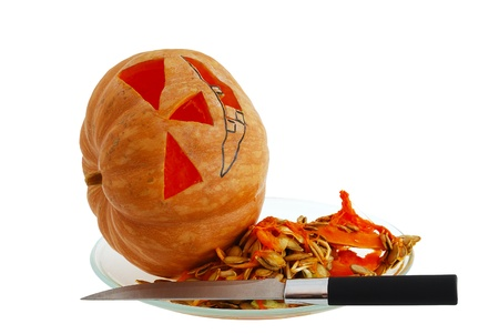 Halloween jack o lantern preparation - carving pumpkin with knife isolated on white background photo
