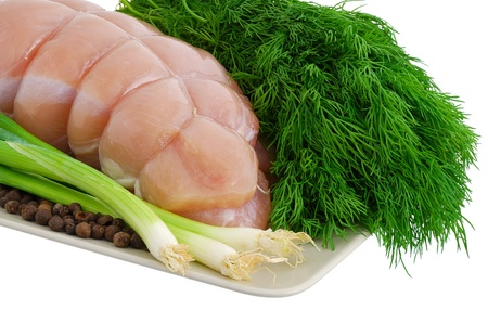 Bound turkey breast with green vegetables on plate isolated on white background