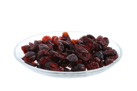 Dried cranberries on glass plate isolated on white background