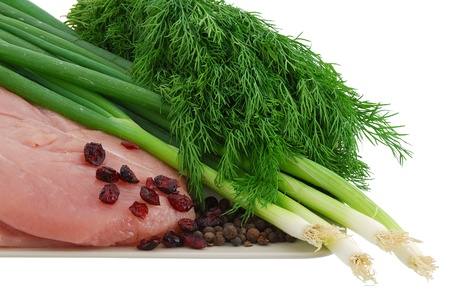 Raw turkey breast with green vegetables and cranberries on plate isolated on white background