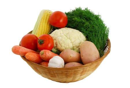 Harvested vegetables mix including  corn, potatoes, garlic, tomatoes, dill  and cauliflower in straw bowl isolated on white background