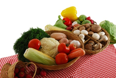 Farmer market stand with rich vegetables selection including  carrot, tomatoes, potatoes, onion, corn, lettuce, cauliflower, dill, sweet pepper  and mushrooms on red-white tablecloth