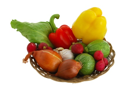 Harvested vegetables mix including  radish, sweet peppers, garlic, onion, lettuce  and squash in straw bowl isolated on white background