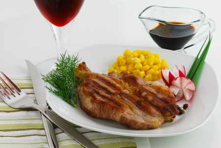 Steak dish garnished by corn, radish and dill served with wine and sauce