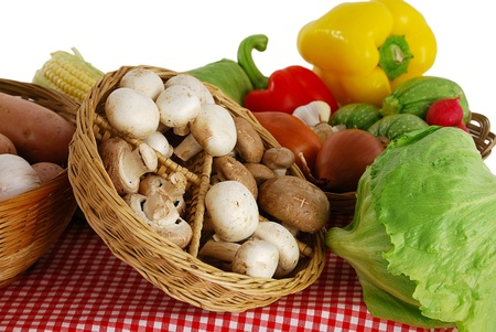 Farmer market stand with rich variety of fruits and vegetables  including  potatoes, onion, corn, lettuce, garlic, squash, sweet pepper  and mushrooms on red-white tablecloth
