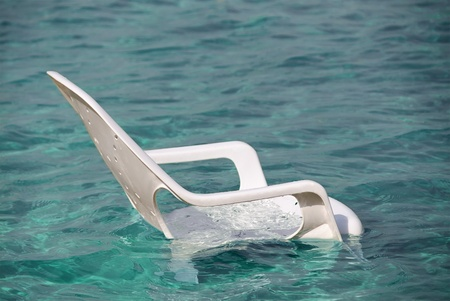 White plastic beach chair in clean blue water