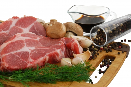 Raw beef steak with portobello mushrooms, pepper, garlic and soy sauce on cutting board isolated on white background