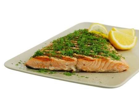 Salmon fish fillet grilled with green vegetables and lemon isolated on white background