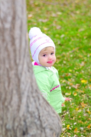 Small beautiful girl in green suit on green glade by autumn peers because of tree  Stock Photo