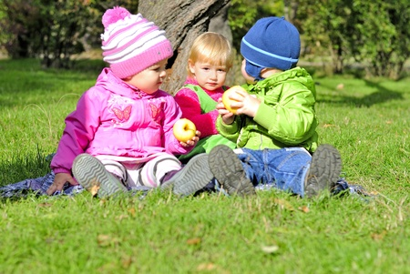 Three small children sit on a green clearing eat apples