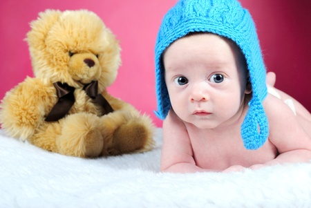 attentiveness: The little boy with the big eyes on a pink background in a dark blue cap with a bear