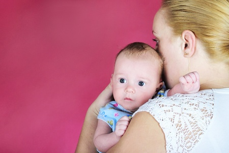 attentiveness: The little boy with the big eyes at mum on hands on a pink background  Stock Photo
