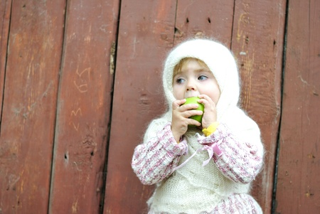 attentiveness: The small beautiful girl sits in a scarf at a fence eats an apple