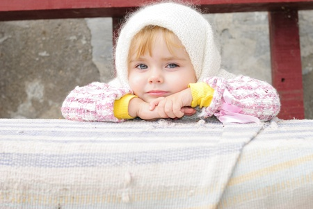 Portrait of the small beautiful girl in a white scarf on a bench  photo