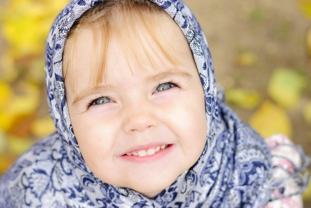 The small beautiful angry girl in a scarf at a fence looks upward with a smile photo
