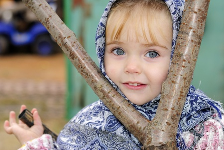 attentiveness: Portrait of the small beautiful girl in a dark blue scarf