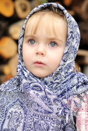 Portrait of the small beautiful girl in a dark blue scarf Stock Photo - 11571774