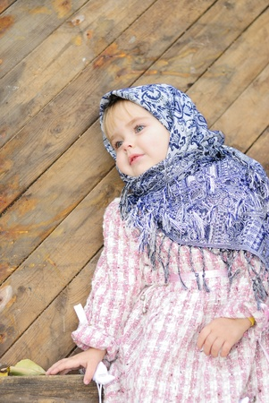 attentiveness: Portrait of the small beautiful girl in a dark blue scarf bent on a fence