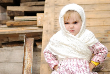 attentiveness: The small beautiful angry girl in a white scarf at a fence