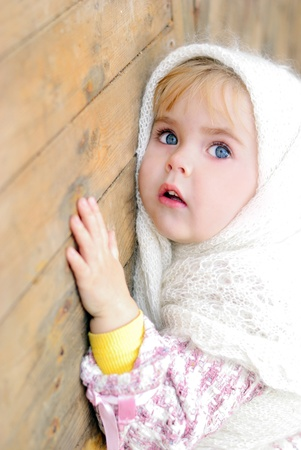 Portrait of the small beautiful girl in a white scarf bent on a fence photo