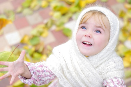 Portrait of the small beautiful girl in a white scarf in the autumn photo