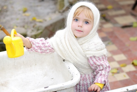 attentiveness: Portrait of the small beautiful girl in a white scarf with a watering can
