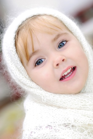 Portrait of the small beautiful girl in a white scarf photo