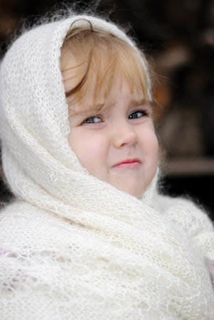 The small sad girl in a white scarf in village photo