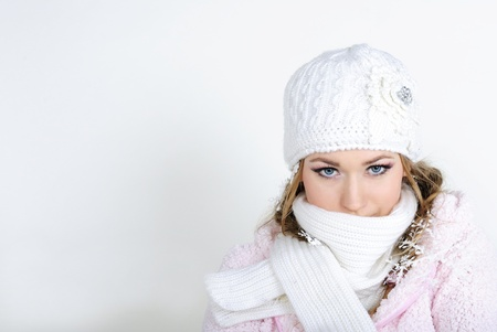 The young beautiful girl in a white cap and a scarf with snowflakes on hair photo