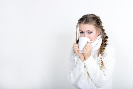 The young beautiful girl in a white scarf with a mug  photo