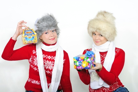 Two young beautiful girls with gifts on a white background photo